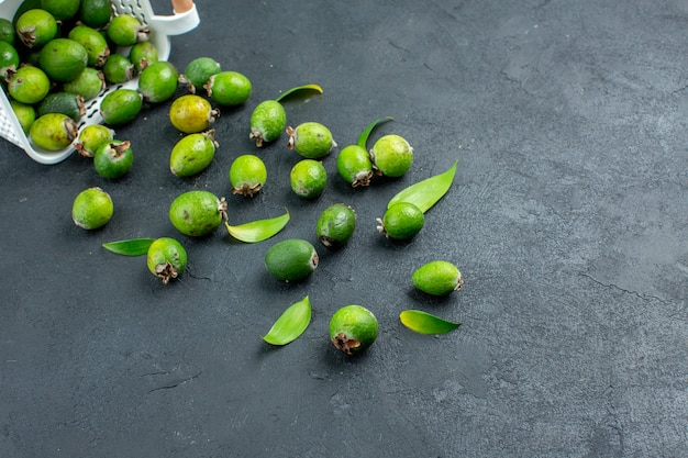 Onderaanzicht verse feijoa's verspreid uit een plastic mand op een donker oppervlak met kopieerruimte