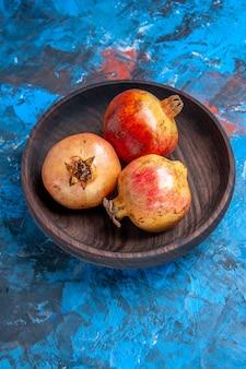 Onderaanzicht verse granaatappels in houten kom op blauwe achtergrond Gratis Foto