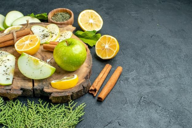Onderaanzicht verse groene appel kaneelstokjes appel- en citroenschijfjes op houten bord gedroogd muntpoeder in kom pijnboomtakken op zwarte tafel kopieerplaats