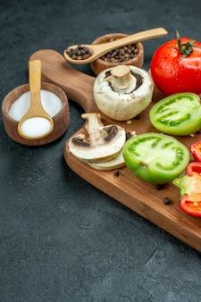 Onderaanzicht verse groenten champignons gesneden rode en groene tomaten paprika op snijplank kommen met zwarte peper en zout houten lepels op zwarte tafel