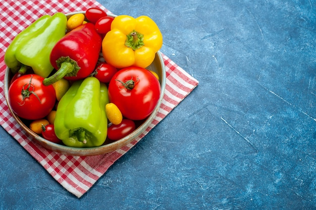 Onderaanzicht verse groenten cherry tomaten cumcuat verschillende kleuren paprika tomaten op schotel op rood en wit geruite keukenhanddoek op blauwe tafel met kopie plaats