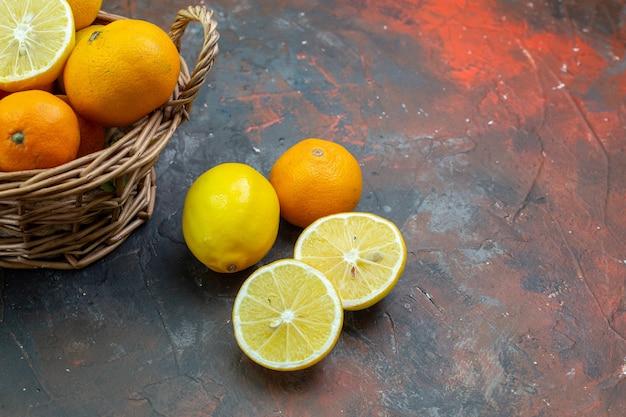 Onderaanzicht verse mandarijnen in rieten mand gesneden citroenen op donkerrode grond met vrije ruimte