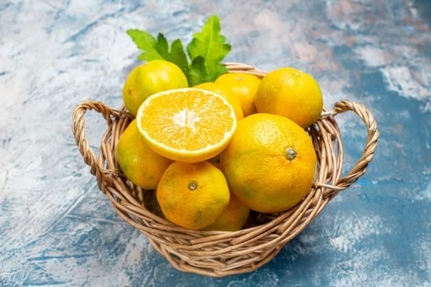 Onderaanzicht verse mandarijnen op rieten mand op blauw wit oppervlak