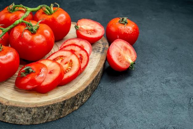 Onderaanzicht verse rode tomaten gehakte tomaten op een houten bord op zwarte tafel vrije ruimte
