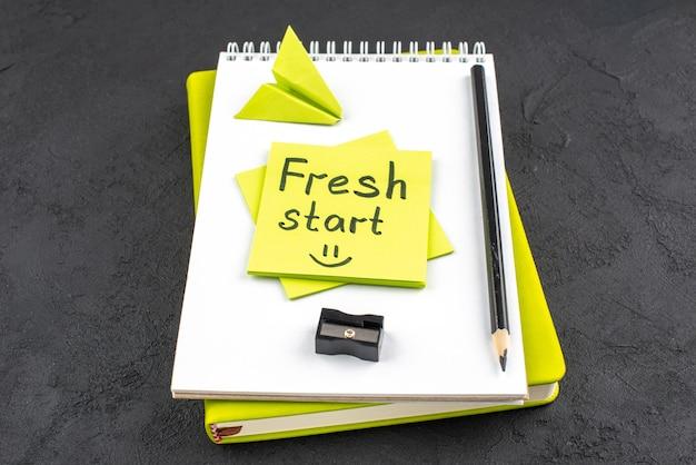 Onderaanzicht verse start geschreven op gele plaknotitie op kladblok zwart potlood en puntenslijper op donkere achtergrond