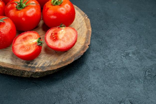 Onderaanzicht verse tomaten op houten bord op donkere tafel met vrije ruimte