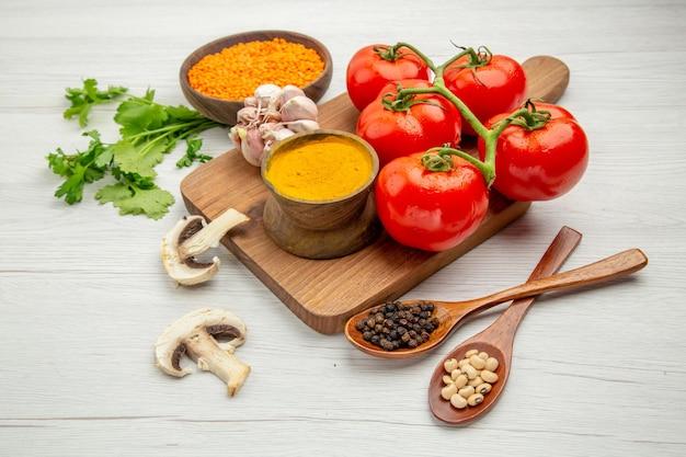 Onderaanzicht verse tomatentak knoflook kurkuma op snijplank champignons zwarte peper en bonen in houten lepels op grijze tafel