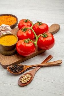 Onderaanzicht verse tomatentak knoflook kurkuma op snijplank houten lepels met zwarte peper en bonen op grijze tafel