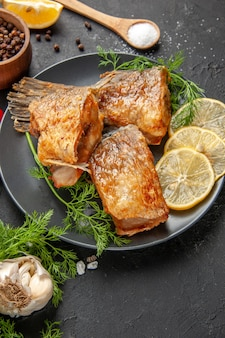 Onderaanzicht vis bak zwarte peper in kom munt citroenschijfjes houten lepel op zwarte tafel