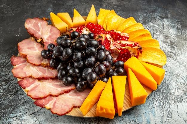 Onderaanzicht vlees plakjes kaas druiven en granaatappel op ovale serveerplank op donkere achtergrond