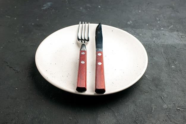 Onderaanzicht vork en mes op witte salade plaat op zwarte ondergrond
