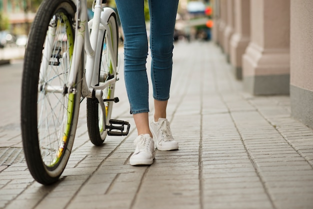 Onderaanzicht vrouw lopen naast de fiets