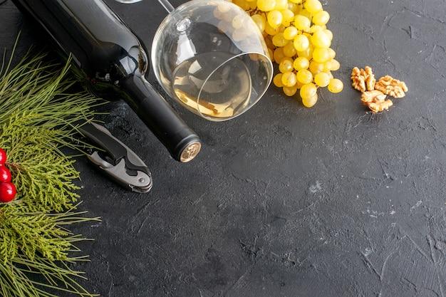 Onderaanzicht wijnglas verse gele druiven walnoot wijnfles kerst rode bessen op zwarte tafel kopieerplaats