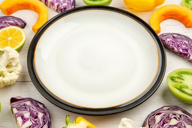 Onderaanzicht witte ronde schotel gesneden groenten op witte houten tafel