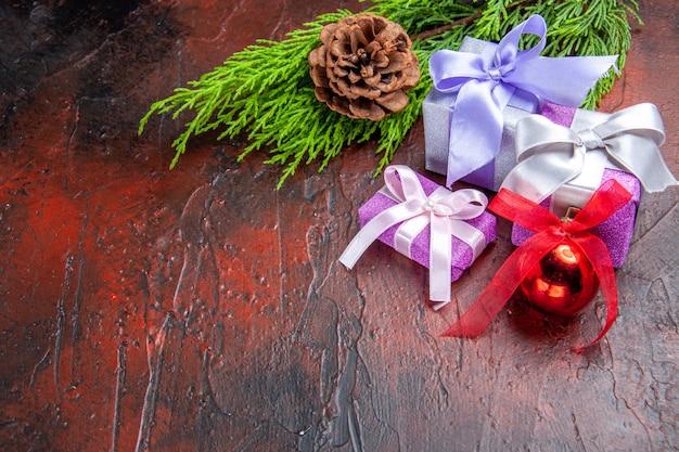Onderaanzicht xmas geschenken boomtak met kegel kerstboom speelgoed op donkerrode achtergrond kopie ruimte nieuwjaarsfoto