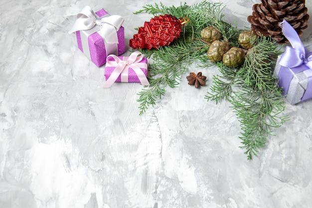 Onderaanzicht xmas geschenken kerstboom speelgoed pijnboom takken op grijze achtergrond vrije ruimte