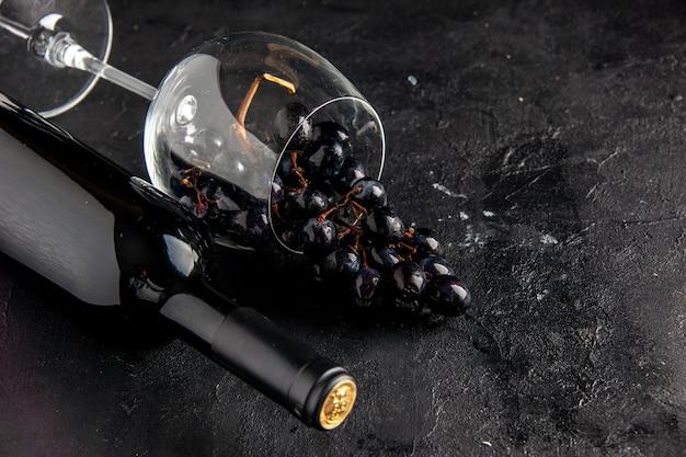 Onderaanzicht zwarte druiven in gekantelde wijnglas wijnfles op donkere tafel
