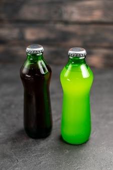 Onderaanzicht zwarte en groene limonade in flessen op donkere ondergrond