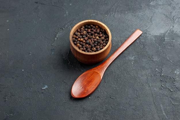 Onderaanzicht zwarte peper kom houten lepel op donkere oppervlakte kopie plaats