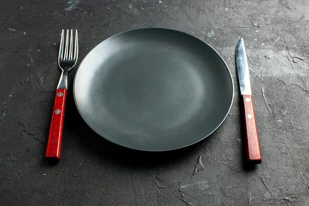 Onderaanzicht zwarte plaatvork en mes op zwart oppervlak