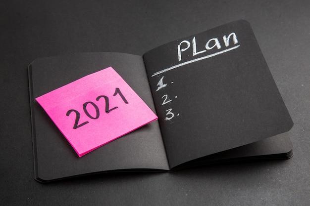 Onderaanzichtplan geschreven op zwart notitieblok geschreven op roze plaknotitie op zwarte achtergrond