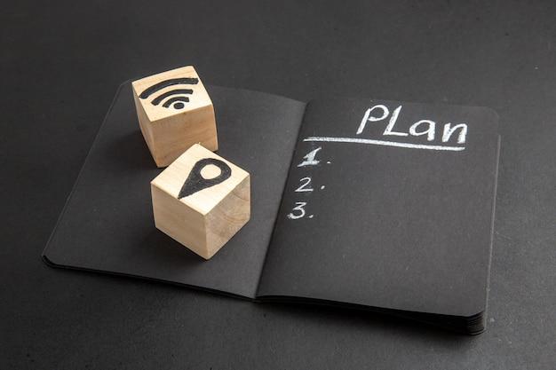 Onderaanzichtplan geschreven op zwarte notitieblok wifi en locatiepictogrammen op houtblokken op zwarte tafel