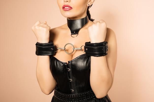 Onderdanig meisje in leer zwart korset, handboeien en kraag wachtend op straf.