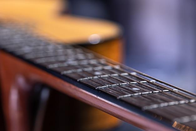 Onderdeel van akoestische gitaar, gitaarhals met snaren in focus.
