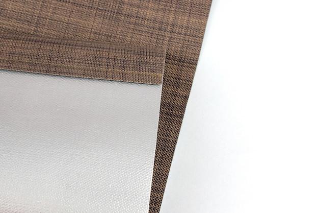 Onderdeel van bruin verduisterend rolgordijn. close-up materiaal van een rolgordijn.