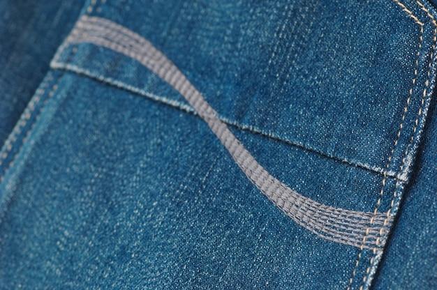 Onderdeel van de blauwe spijkerbroek met achterzakken, close-up