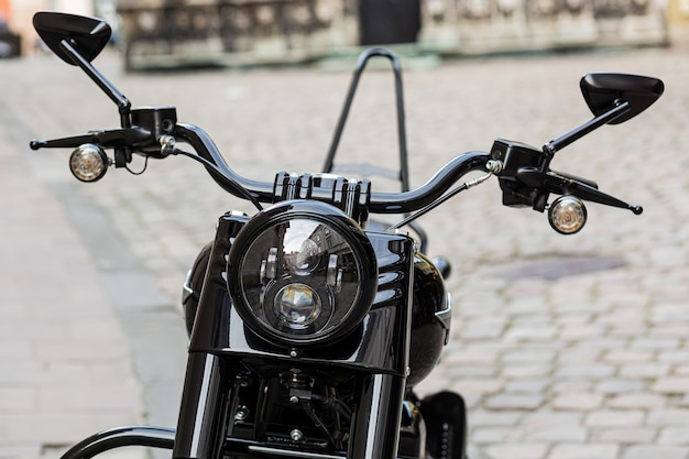 Onderdeel van een retro zwarte motorfiets met een grote koplamp