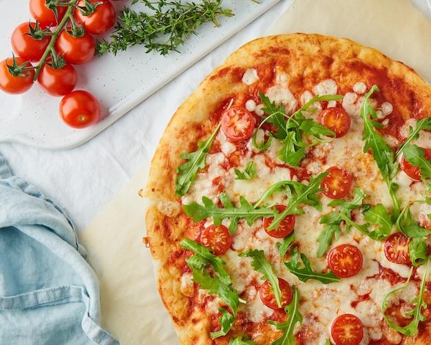 Onderdeel van rustieke italiaanse huisgemaakte pizzadeeg margherita overgoten met pizzasaus van tomaten uit blik, mozzarella kaas en rucola
