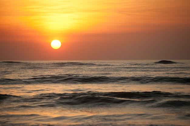 Ondergaande zon over de kalme oceaan met een oranje gloed