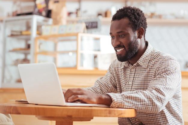 Ondergedompeld in werk. vrolijke jonge man zit aan de tafel in het koffiehuis en werkt op de laptop terwijl hij aangenaam lacht