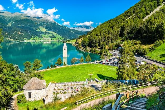 Ondergedompelde klokkentoren van curon en een kerkhof in graun im vinschgau aan het meer van reschen in zuid-tirol, italië
