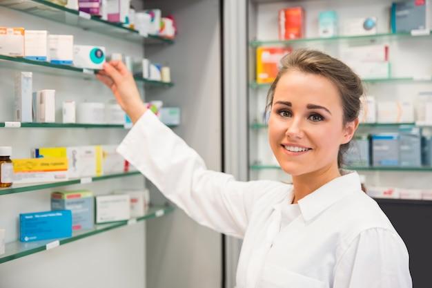 Ondergeschikte apotheker die geneeskunde van plank neemt