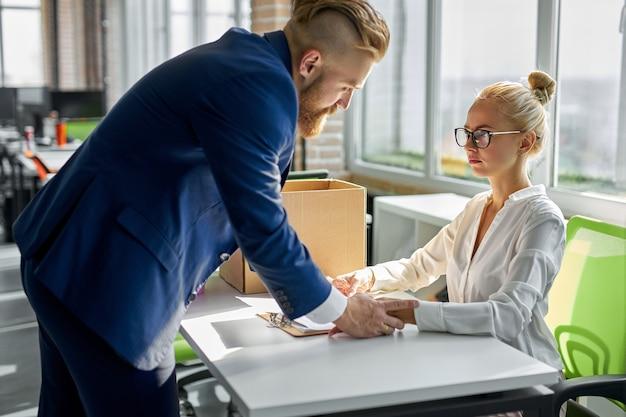 Ondergeschikte relaties. volwassen man toont zijn seksuele interesse terwijl hij de vrouw van de werknemer lastig valt, haar hand aanraakt