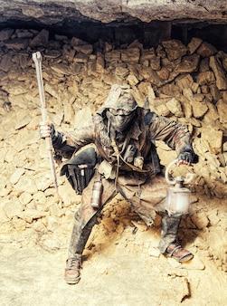 Ondergronds post-apocalyptisch wezen met zelfgemaakte wapens en lantaarn
