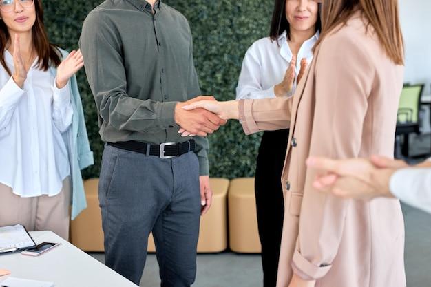 Onderhandeling begint met succesvolle zakenlieden leiders van zakelijke partijen handen schudden, mannelijke baas groet bedrijf klant jonge ondernemers verzamelden zich in moderne bestuurskamer, problemen oplossen