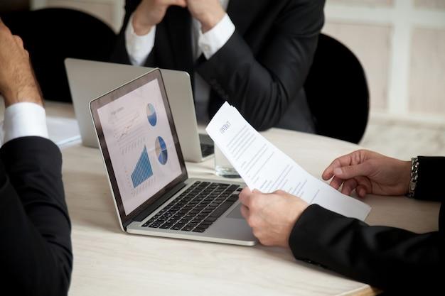 Onderhandelingen op contract tijdens vergadering van drie partners, close up