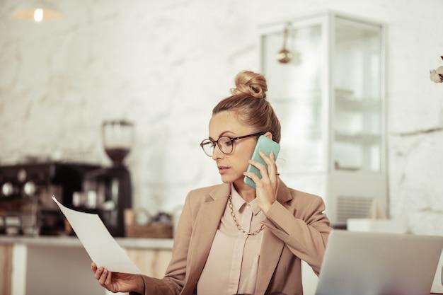 Onderhandelingen voeren. ernstige slimme zakenvrouw praten door haar smartphone kijken naar een vel papier in haar hand.