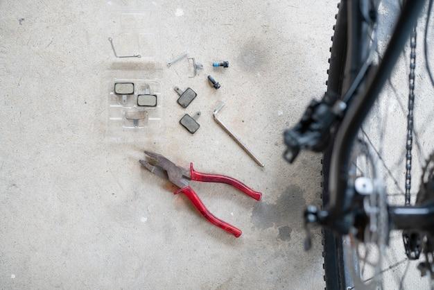 Onderhoud van een mtb hydraulische schijfremklauw: reparateur die een hydraulische achterste schijfremklauw op een mountainbike houdt.