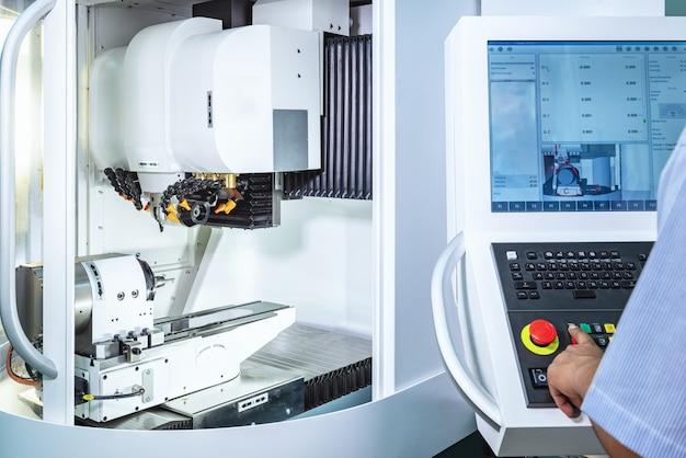 Onderhoudsingenieur die industrieel robotachtig holdings automobieldeel met cnc machine controleren