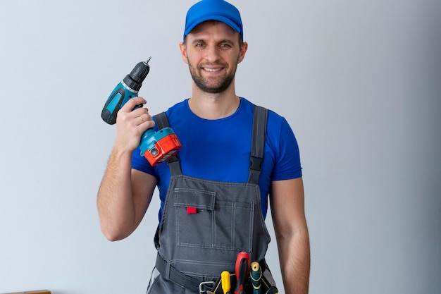 Onderhoudsmedewerker in uniform houdt een schroevendraaier vast en kijkt naar de cameraklusser die een gereedschapsriem draagt