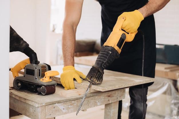 Onderhoudsmens die een machtszaag gebruiken om meubilair te bevestigen