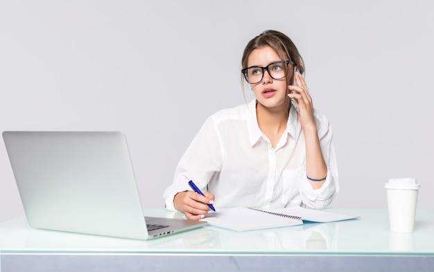 Onderneemster bij haar bureau met laptop en sprekende telefoon die op witte achtergrond wordt geïsoleerd