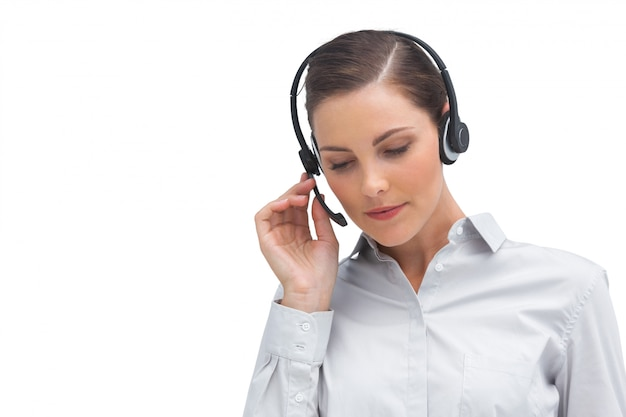 Onderneemster die aan bezoeker op hoofdtelefoon luistert