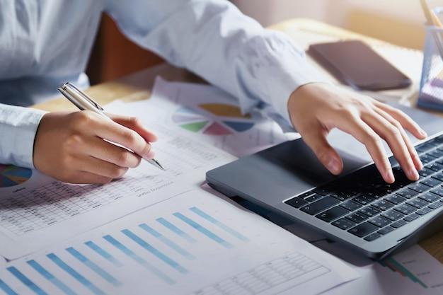 Onderneemster die aan bureau werken die laptop voor controlegegevens van financiën in bureau met behulp van