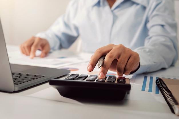 Onderneemster die aan bureau werkt dat calculator gebruikt die financiënboekhouding in bureau analyseert