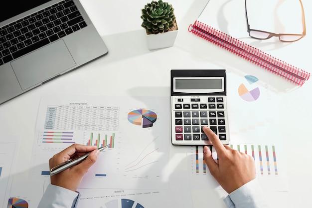 Onderneemster die aan bureau werkt die calculator en laptop met behulp van die financiënboekhouding in bureau analyseren